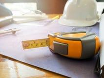 Tape measure on blueprints stock photo
