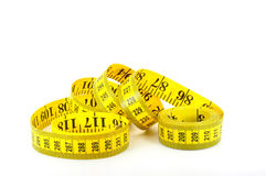 Tape measure coiled on white. Tape measure with inches and centimeters uncurled and isolated on white Royalty Free Stock Photo