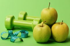 Tape measure in cyan color near barbells and juicy apples. Close up. Dumbbells in bright color, measure tape and fruit pyramid on green background. Healthy stock photos