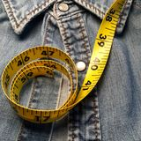 Tape measure and denim shirt. Royalty Free Stock Photography