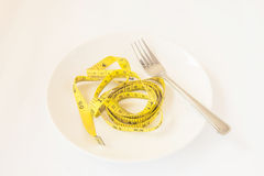 Tape measure with fork on plate Royalty Free Stock Image