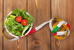Tape measure and healthy food over wooden table Stock Photo