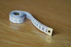 Tape measure measuring length in centimeters and meters, frequently used for measuring the perimeter of human body during the die Royalty Free Stock Photo