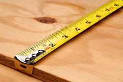 Tape measure measuring wood Royalty Free Stock Photo