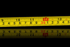 Tape measure in millimetres and inches on black Stock Image