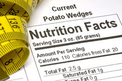 Tape Measure next to Nutrition Facts. Yellow tape measure next to nutrition information on packaging in the USA Stock Images