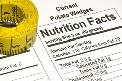Tape Measure next to Nutrition Facts. Yellow tape measure next to nutrition information on packaging in the USA Royalty Free Stock Photography