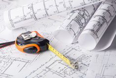 Tape measure over a construction plan drawing Royalty Free Stock Photo
