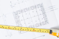 Tape measure over a construction plan drawing Royalty Free Stock Images