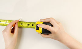 Tape Measure and Pencil preparing to mark interior wall Stock Photography