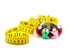 Tape measure with pin cushion. Tape measure coiled with pin cushion and pins isolated on white Royalty Free Stock Images