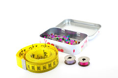 Tape measure pins and bobbins. Tape measure coiled with pins in tin and bobbins isolated on white Royalty Free Stock Image