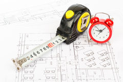 Tape measure with red alarm clock, close up view Stock Images