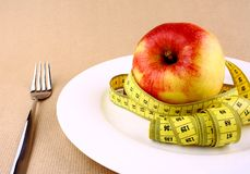 Tape measure and red apple on white plate with fork Royalty Free Stock Images