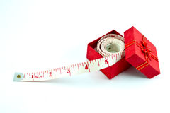 Tape measure in a red gift box. On white background Royalty Free Stock Image