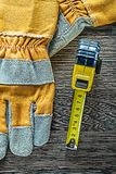 Tape measure safety gloves on wooden board Stock Photos
