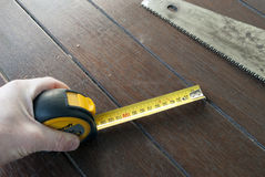 Tape measure and saw on floor Royalty Free Stock Photos