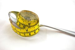 Tape Measure on Spoon Dieting. This still life represents dieting with a tape measure on a silver spoon, isolated on a white background Stock Images