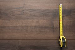 Tape measure on the brown wooden table with copy space royalty free stock photos