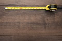 Tape measure on the brown wooden background stock photo