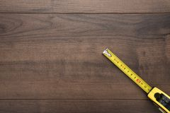 Tape measure on the brown wooden background stock images