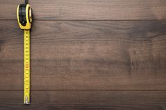 Tape measure over wooden background with copy space. top view photo of yellow tape measure on brown table royalty free stock image
