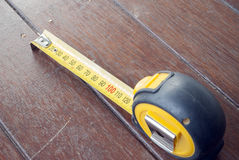 Tape measure on timber floor Stock Images