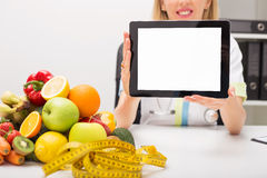 Tape measure and vegetables on table  and doctor holding tablet with blank screen Stock Image