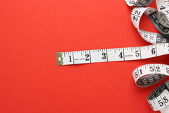 Tape Measure. A white tape measure with both inches and centimetres on a red paper background Royalty Free Stock Image