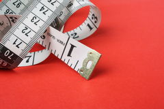Tape Measure. A white tape measure with both inches and centimetres on a red paper background Royalty Free Stock Images