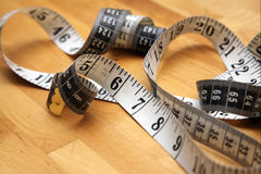 Tape measure on wooden floor Royalty Free Stock Photography