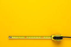 Tape measure on the yellow background. With copy space Royalty Free Stock Photography