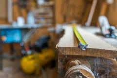 Free Tape Measurer On Long Oak Board In A Small Wood Workshop Stock Image - 137648061