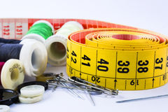 Tape measuring  and spools of threads backgroun white. Yellow tape measuring  and spools of threads backgroun white Stock Images