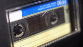 Tape Recorder Plays Audio Cassette inserted therein. Vintage Audio Tape. Macro static camera view of retro audio cassette tape with a blank label used for stock video footage