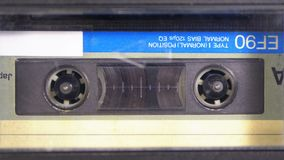 Tape Recorder Plays Audio Cassette inserted therein. Vintage Audio Tape. Macro static camera view of retro audio cassette tape with a blank label used for stock footage
