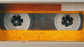 Tape Recorder Plays Audio Cassette inserted therein. Vintage Audio Tape. Macro static camera view of retro yellow audio cassette tape with a blank label used stock video footage