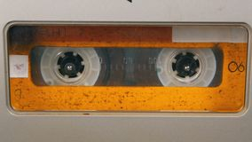 Tape Recorder Plays Audio Cassette inserted therein. Vintage Audio Tape. Macro static camera view of retro yellow audio cassette tape with a blank label used stock video