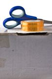 Tape with scissors on cardboard box Royalty Free Stock Images