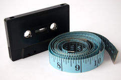 Tape vs Tape. This is an image of measuring tape and a cassette tape royalty free stock photography