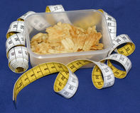 Taped fatbox. Measuring tape and a box with crisps Stock Photo