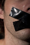 Taped mouth. Man with masking tape on his mouth Royalty Free Stock Photography