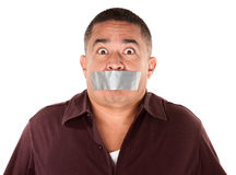 Taped Mouth Hispanic Man. Worried Hispanic man with duct tape over his mouth Royalty Free Stock Photo