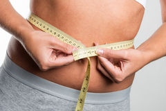 Tapeline measures belly of young woman Royalty Free Stock Photos