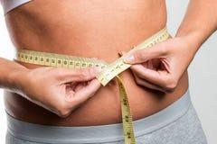 Tapeline mide la cintura de la mujer joven Fotografía de archivo