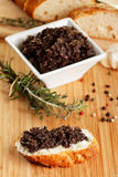 Tapenade. A small bowl of tapenade or olive paste with bread Stock Photo