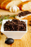 Tapenade. A small bowl of tapenade or olive paste with bread Stock Image