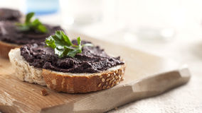Tapenade olive avec le persil frais sur une tranche de pain image stock