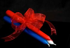 Taper Candles Red, White and Blue. This photo is three tapered candles, one red, white and blue each, tied together with a red shiny sheer bow against a black Royalty Free Stock Photography