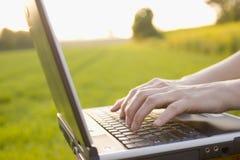 Taper sur un ordinateur portatif à l'extérieur Photographie stock libre de droits